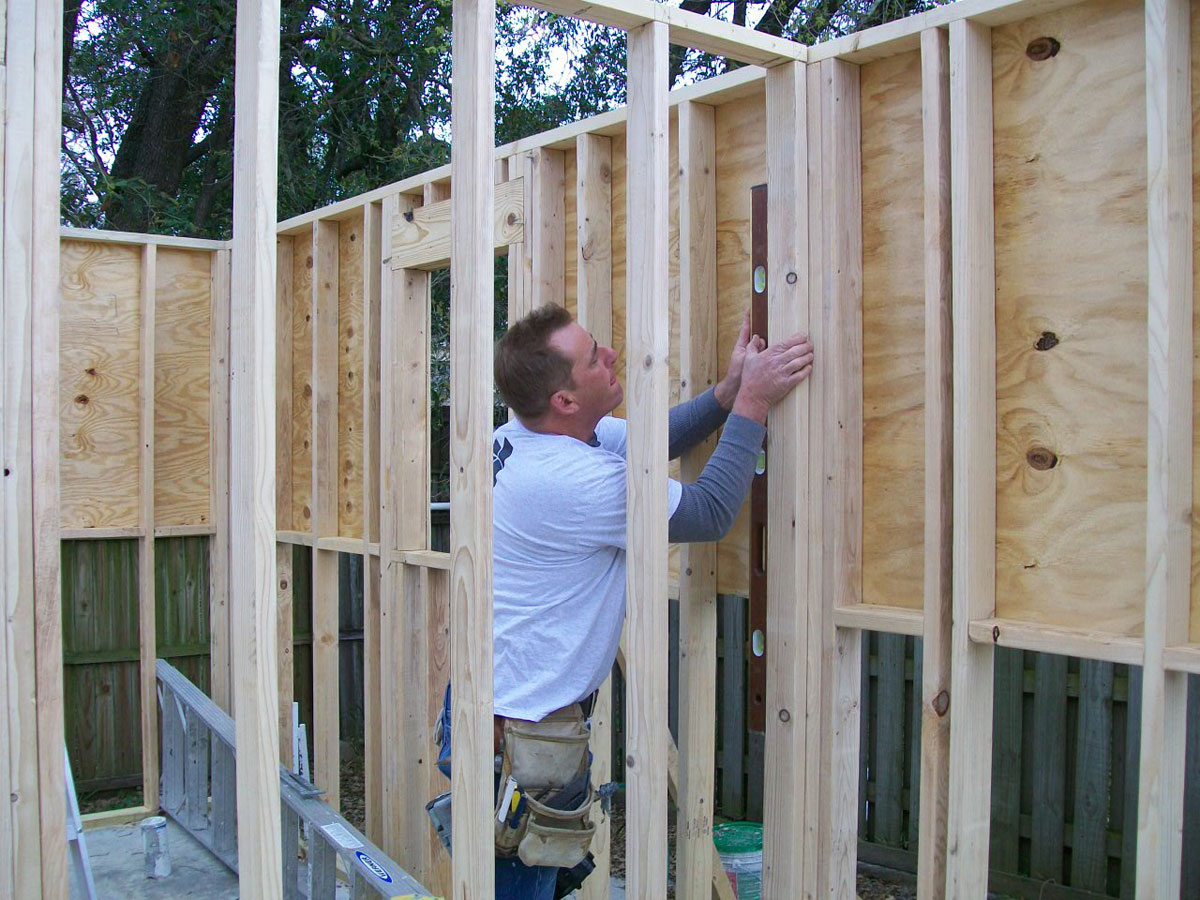 Here is one of our garage construction experts checking the alignment along one of on the walls.
